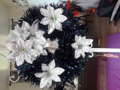 Polystyrene wreath decorated with Blue tinsel and decorated with silver poinsettias - £15.00 each