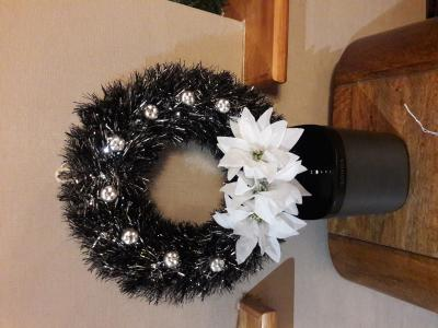 Polystyrene wreath decorated with black and silver tinsel, white poinsettias and silver apples - £15.00 each